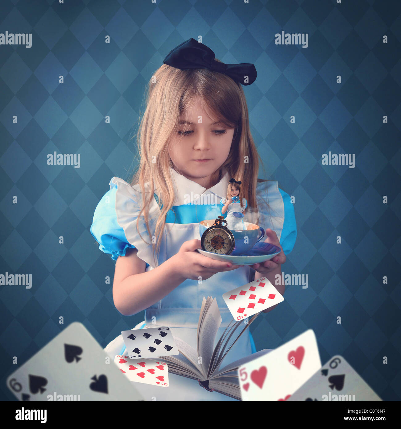 Una bambina è in possesso di una tazzina con carte da gioco e un libro. Il bambino è dentro la coppa per Immagini Stock