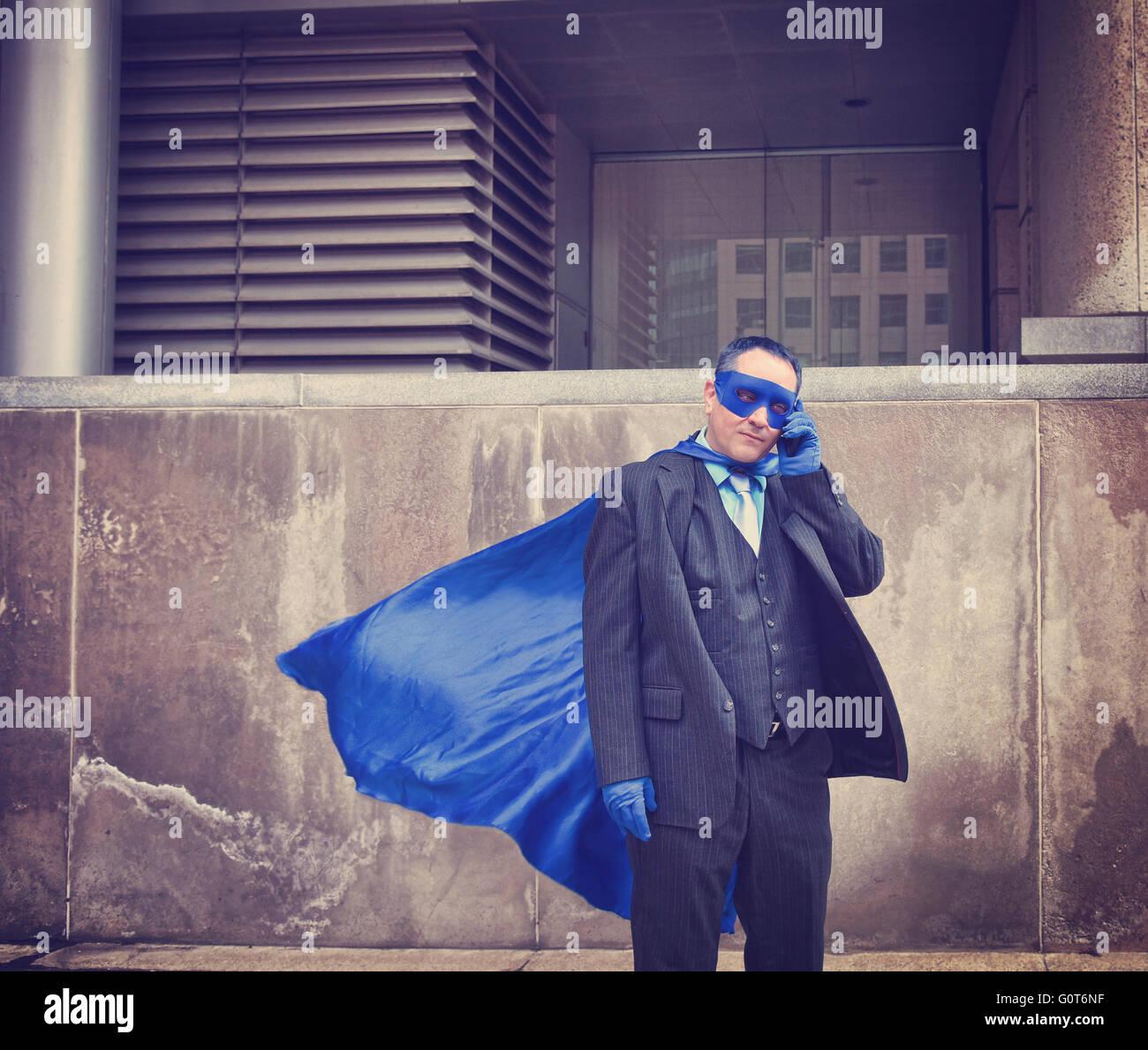 Un uomo di affari è vestito come un super eroe utilizzando un telefono in città per un unico umoristico Immagini Stock