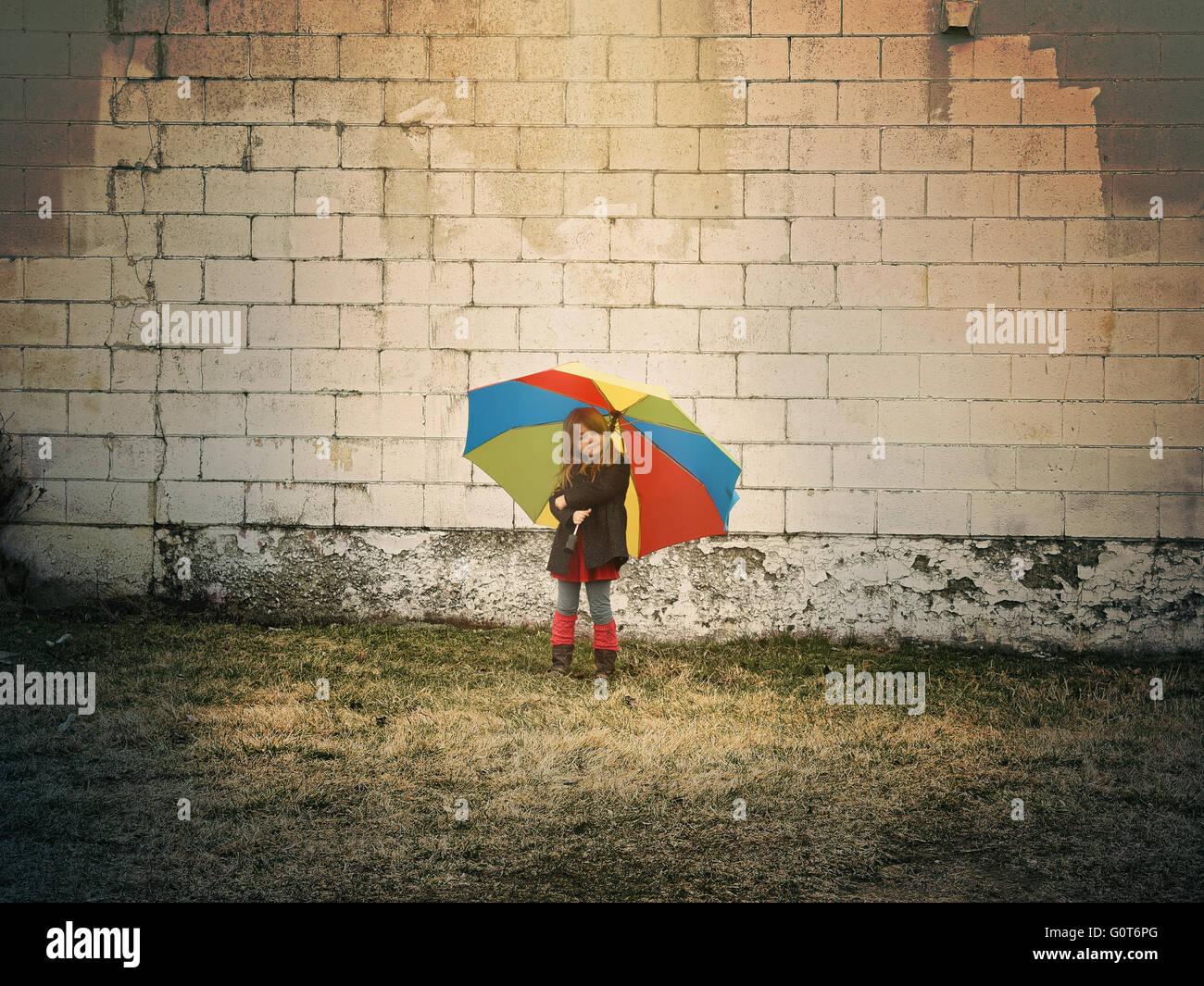 Un bambino è in piedi contro un muro di mattoni tenendo un ombrello arcobaleno al di fuori di una speranza, Immagini Stock