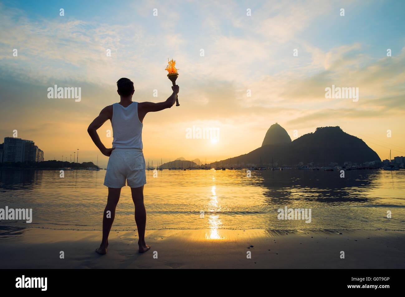 Atleta in piedi con la torcia sport contro un tramonto panoramico vista di Sugarloaf Mountain e il Botafogo Bay Immagini Stock