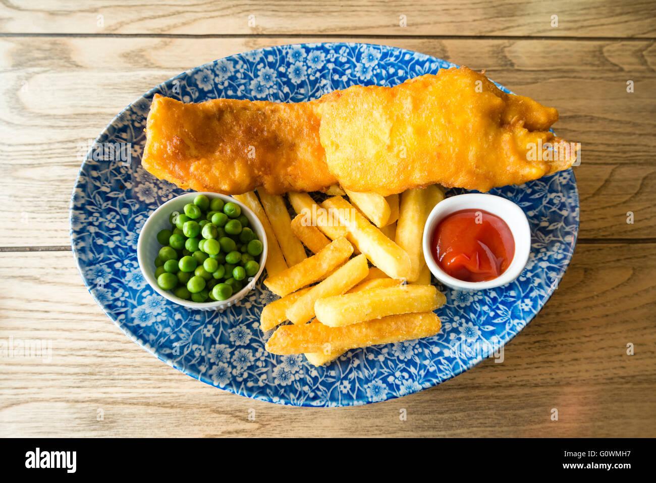 Fish & Chips con piselli e ketchup, pranzo in stile pub, UK. Immagini Stock