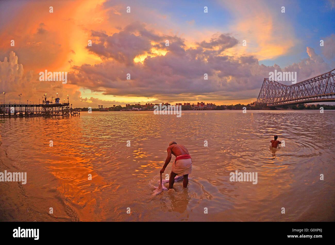 La gente la balneazione sul fiume Hoogly al tramonto con quella di Howrah Bridge a destra, Calcutta, Bengala Occidentale Foto Stock