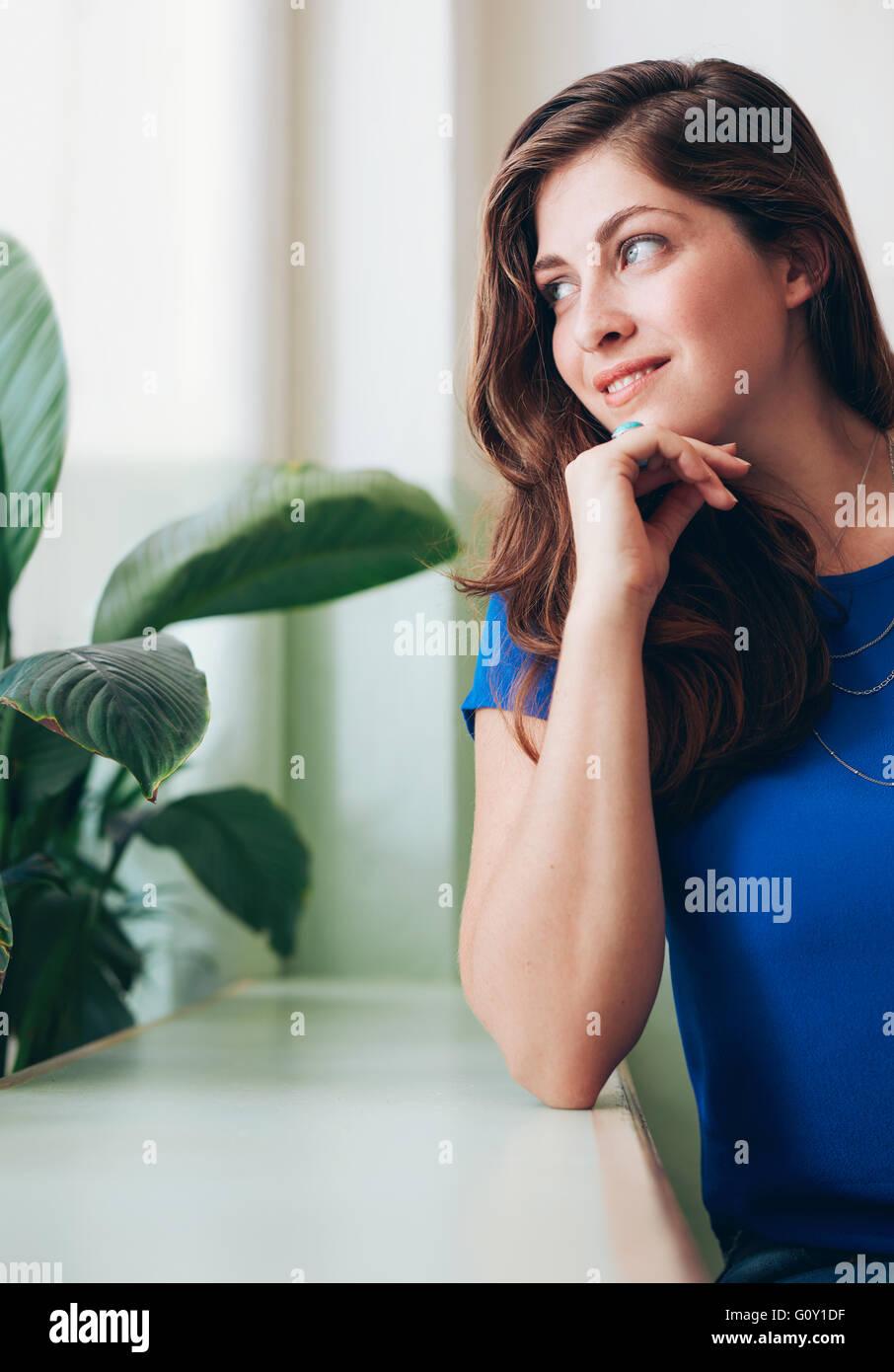 Ritratto di giovane e bella donna seduta a un contatore. Femmina caucasica seduto con le mani sul mento e guardando Immagini Stock