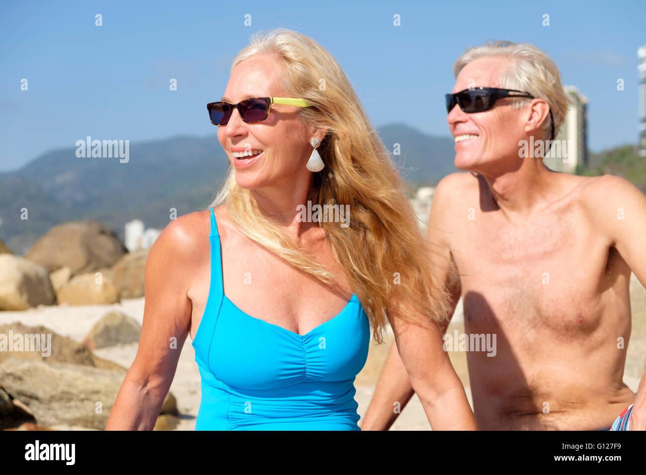 f2fdcab5d991 Senior l uomo e la donna in costume da bagno seduto su una spiaggia in  Messico. Close up ritratto.