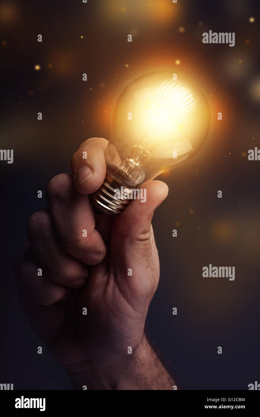 Energia creativa e la potenza delle nuove idee, la mano che tiene la luce della lampadina, dai toni rétro immagine, Immagini Stock