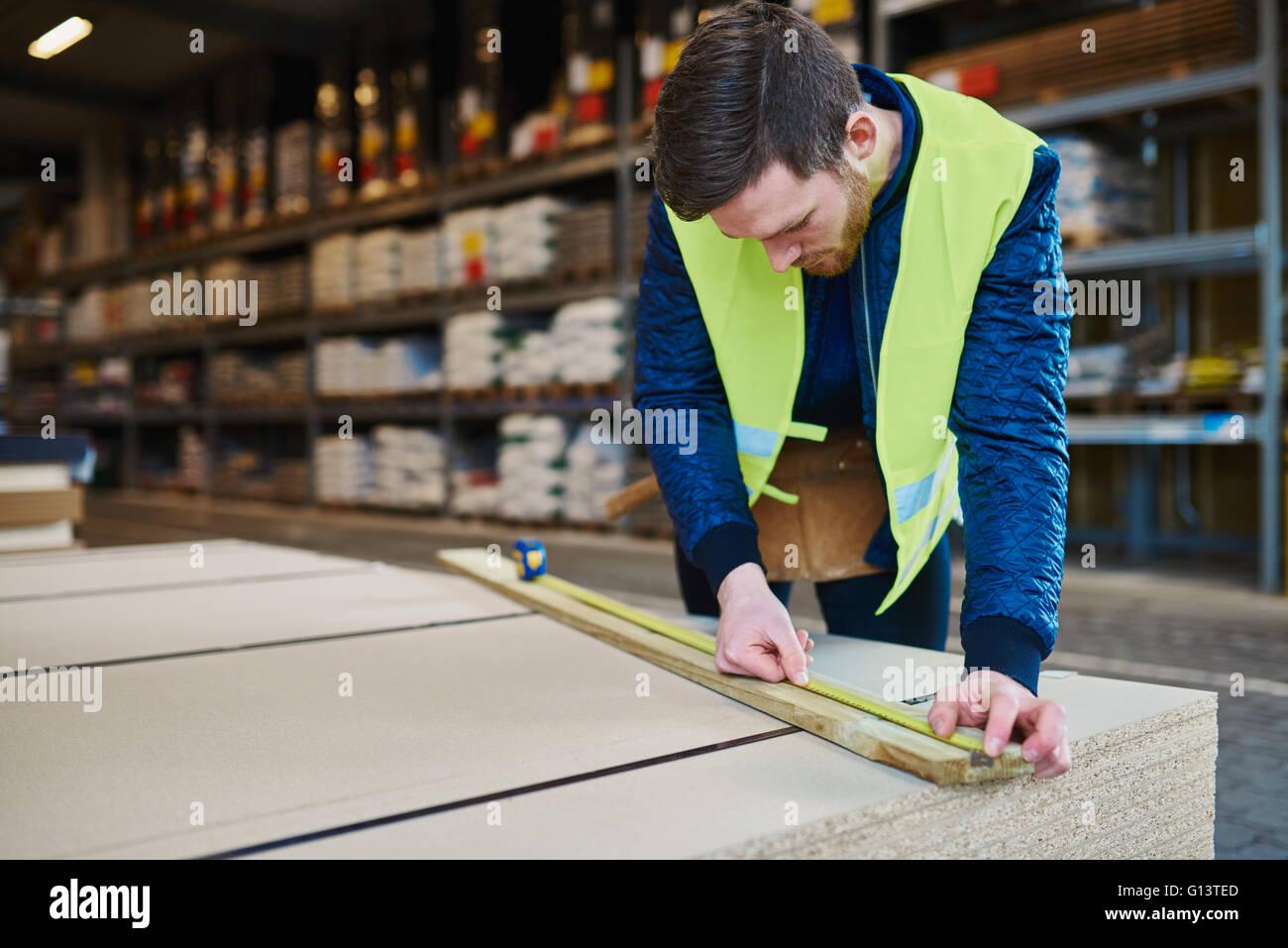 Tuttofare lavora in magazzino la misurazione di un pezzo di legno Immagini Stock