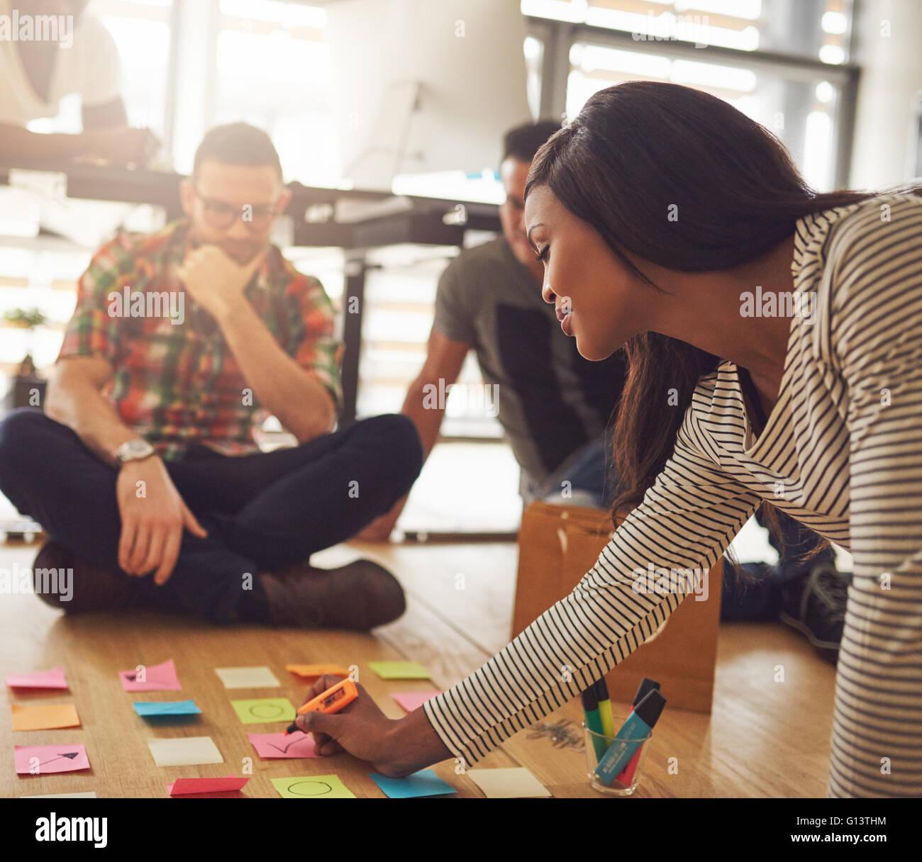 Femmina proprietario di affari la scrittura su varie note adesive per i lavoratori sul pavimento in un ufficio di Immagini Stock