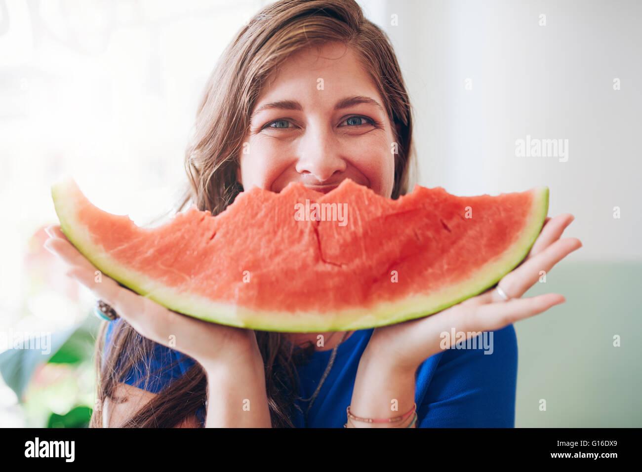 Ritratto di felice giovane donna in possesso di una fetta di cocomero davanti al suo volto. Immagini Stock