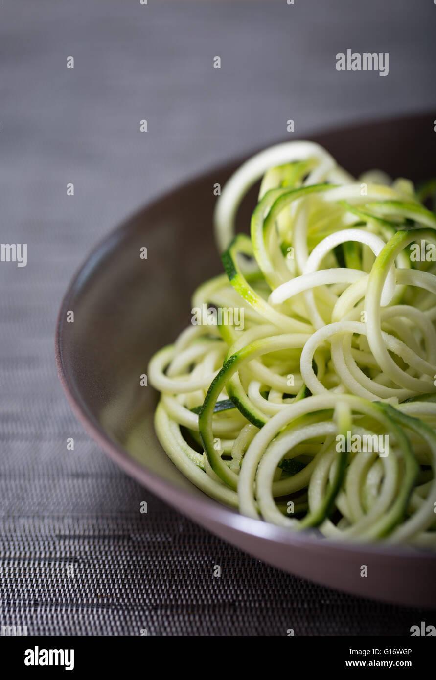 Una ciotola di zucchine (zucchine) tagliatelle (spaghetti) realizzato utilizzando un spiralizer Immagini Stock