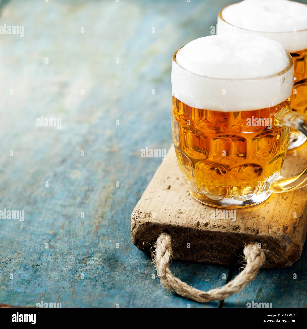 Una birra su di uno sfondo di legno con copyspace Immagini Stock