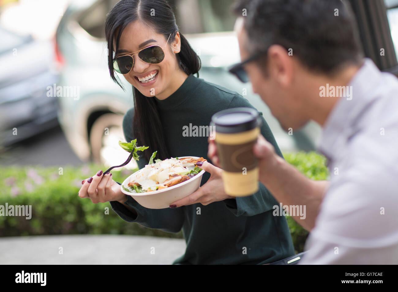 Coppia al cafè sul marciapiede godendo il pranzo Immagini Stock
