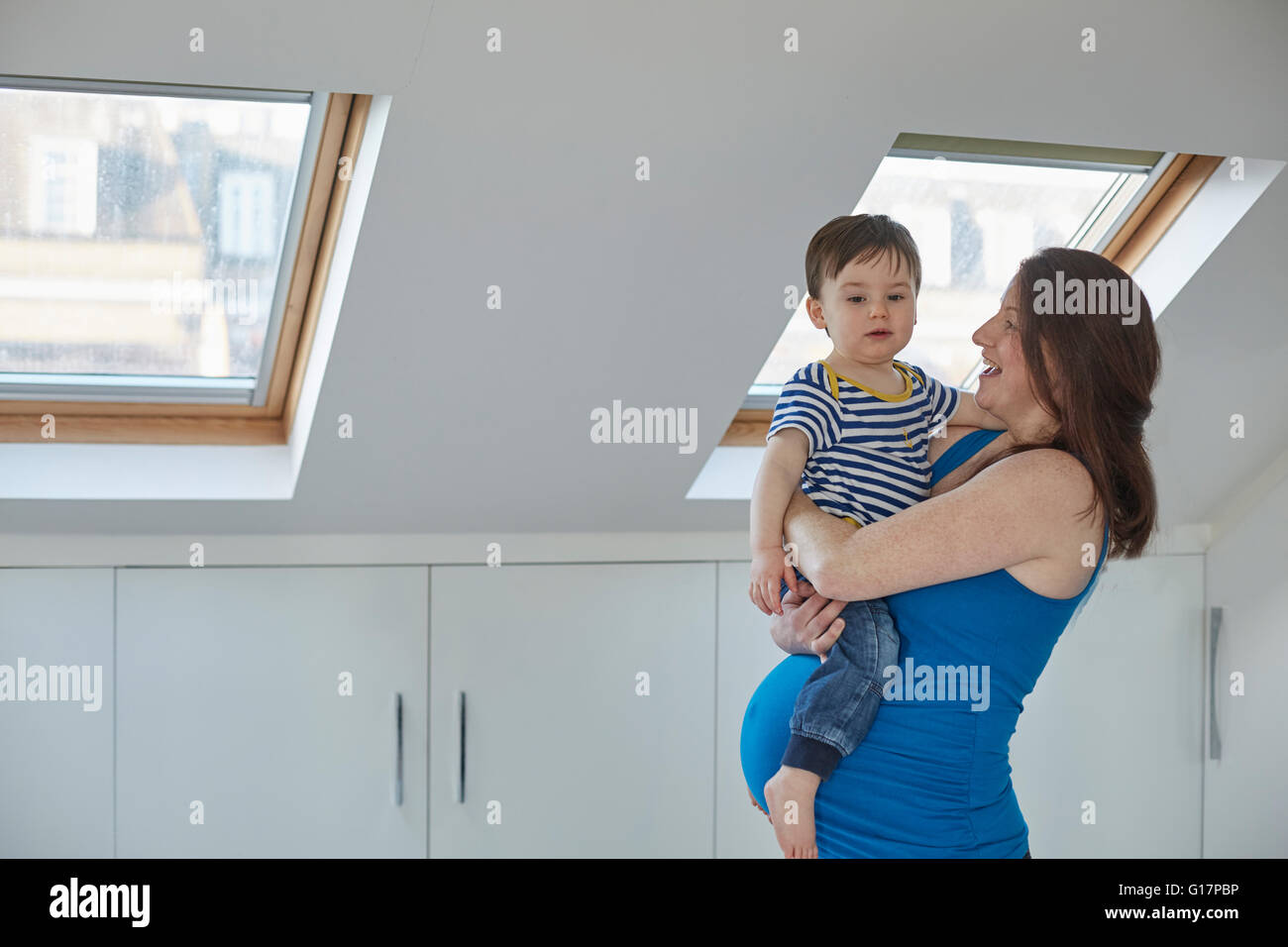 Vista laterale della donna incinta holding baby boy Foto Stock