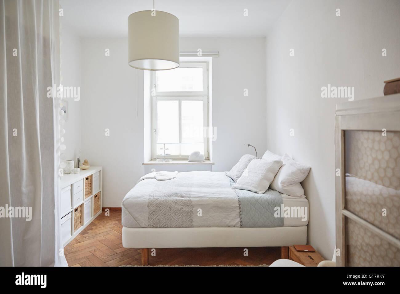 Colorate di bianco camera da letto con pavimento in parquet, letto e ...