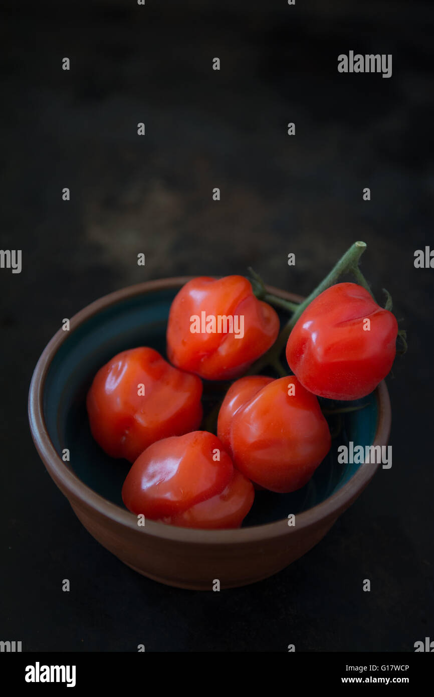 I pomodori in un piccolo recipiente con sfondo scuro Immagini Stock