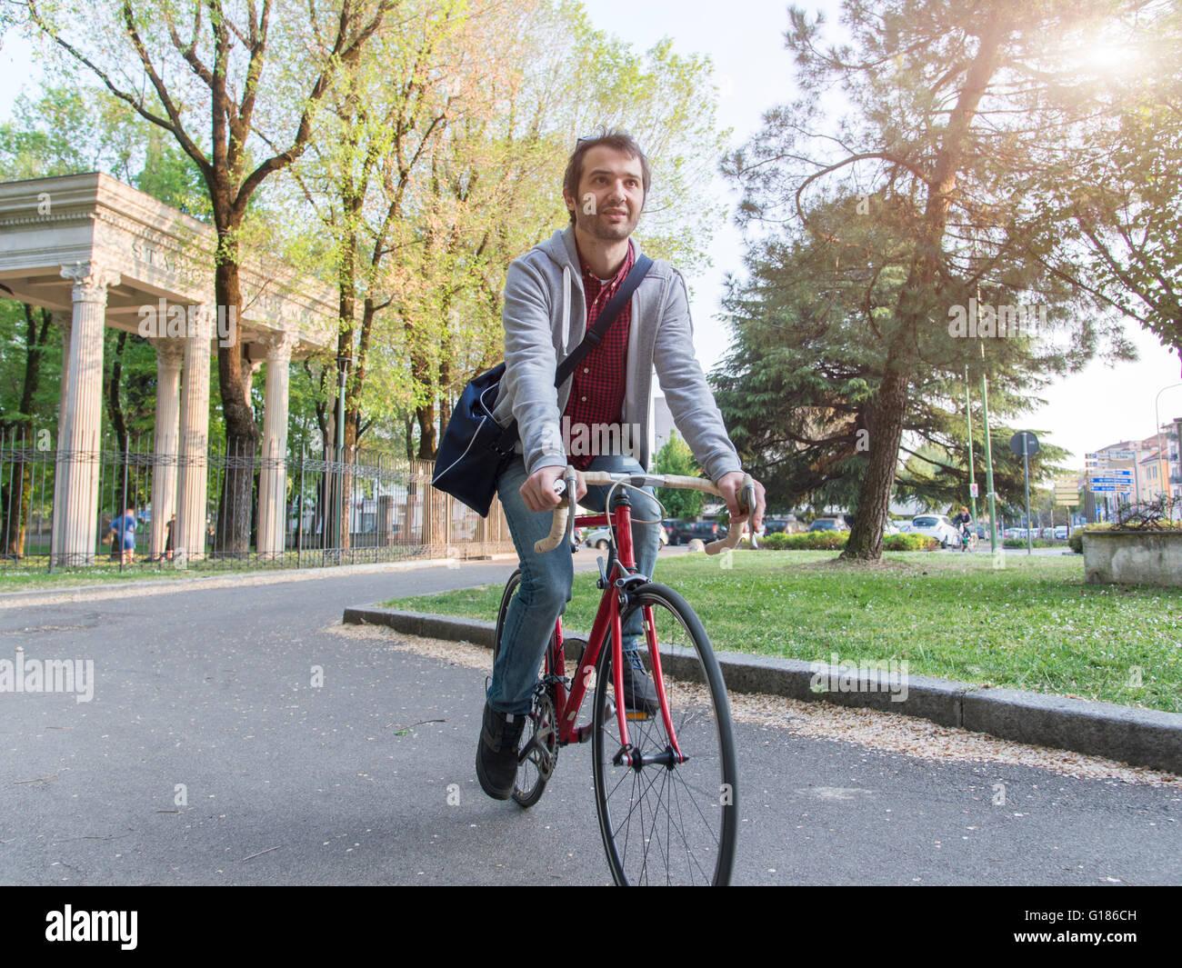 Uomo in bicicletta nel parco della città in una giornata di sole Immagini Stock