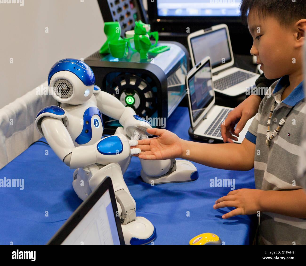 Bambino interagendo con robot umanoide a Science and Engineering Fair - USA Immagini Stock