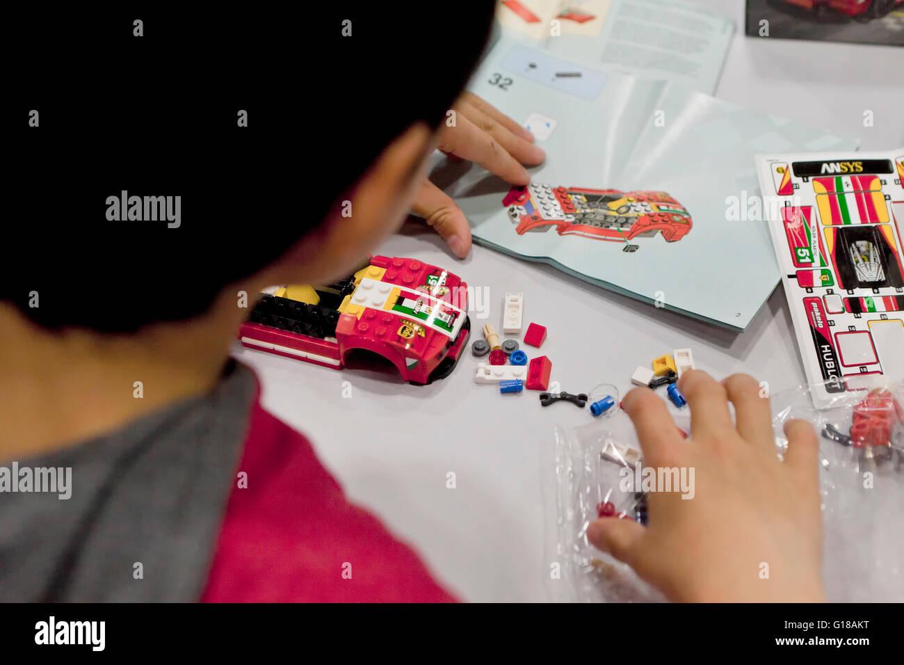 Bambino costruire un Lego auto sportiva utilizzando il manuale di istruzioni - USA Immagini Stock
