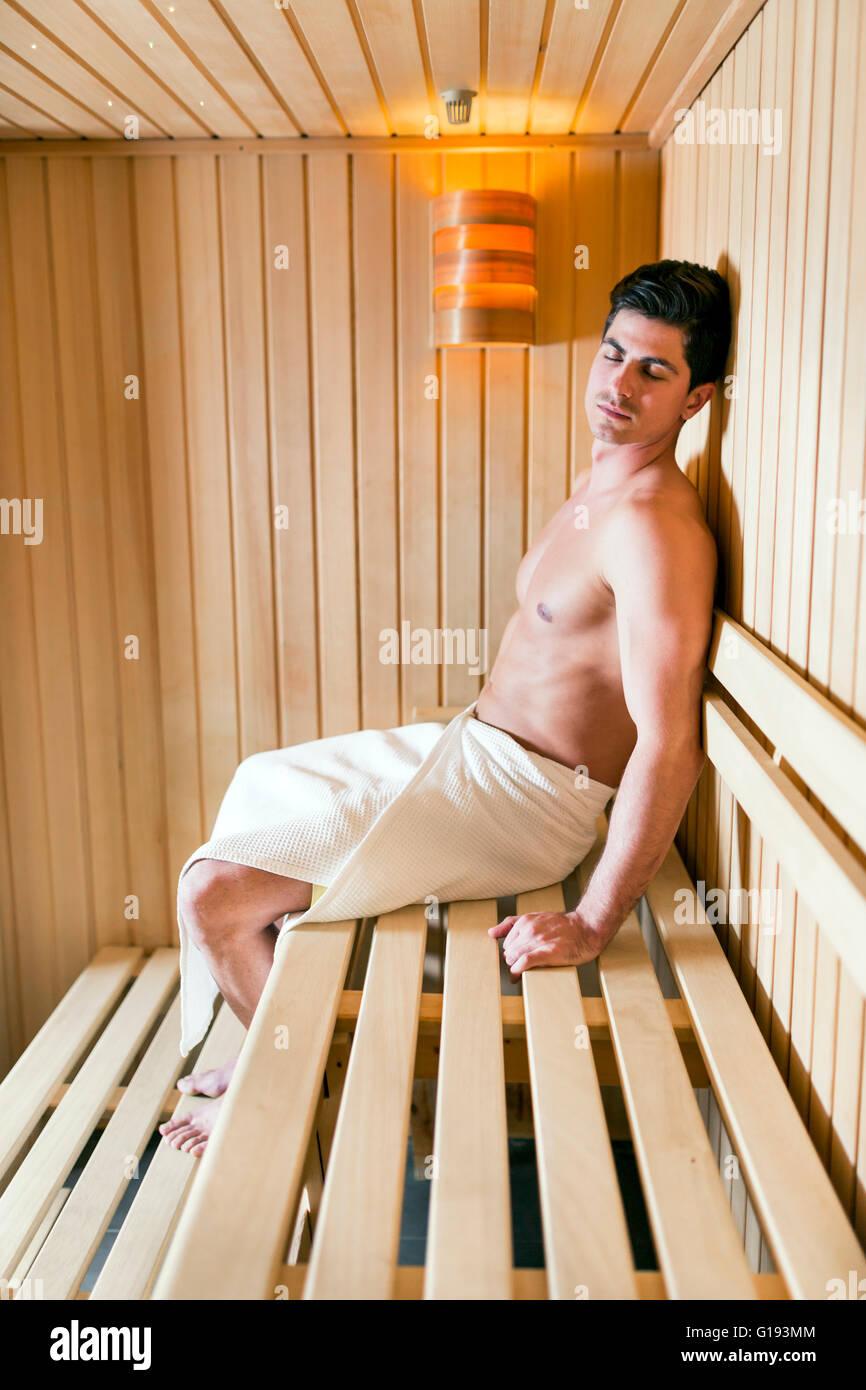 Uomo bello rilassarsi in una sauna con asciugamano avvolto intorno alla vita Immagini Stock