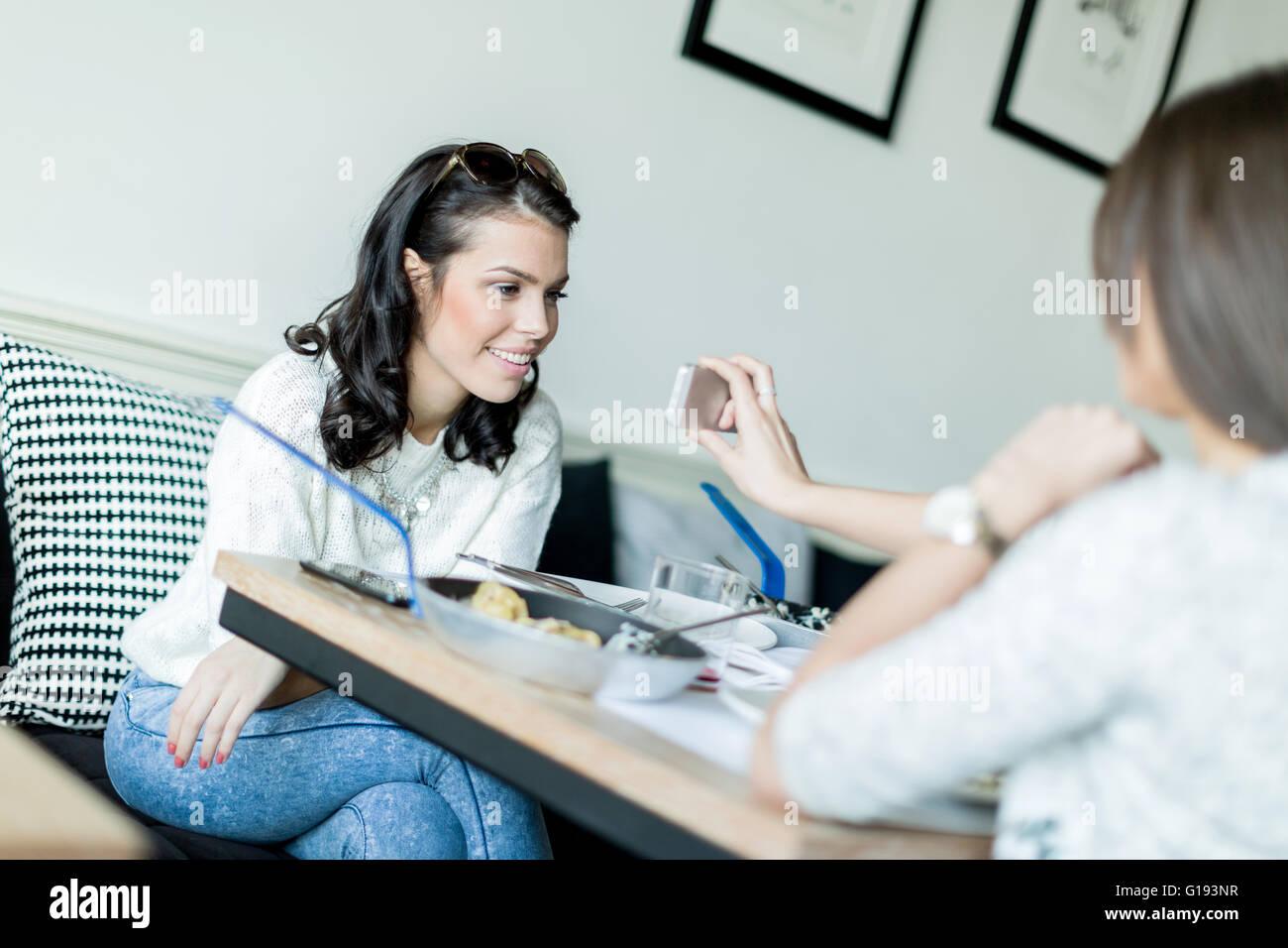 Bella giovane donna sorridente con gioia perché la cella di divertenti contenuti del cellulare Immagini Stock