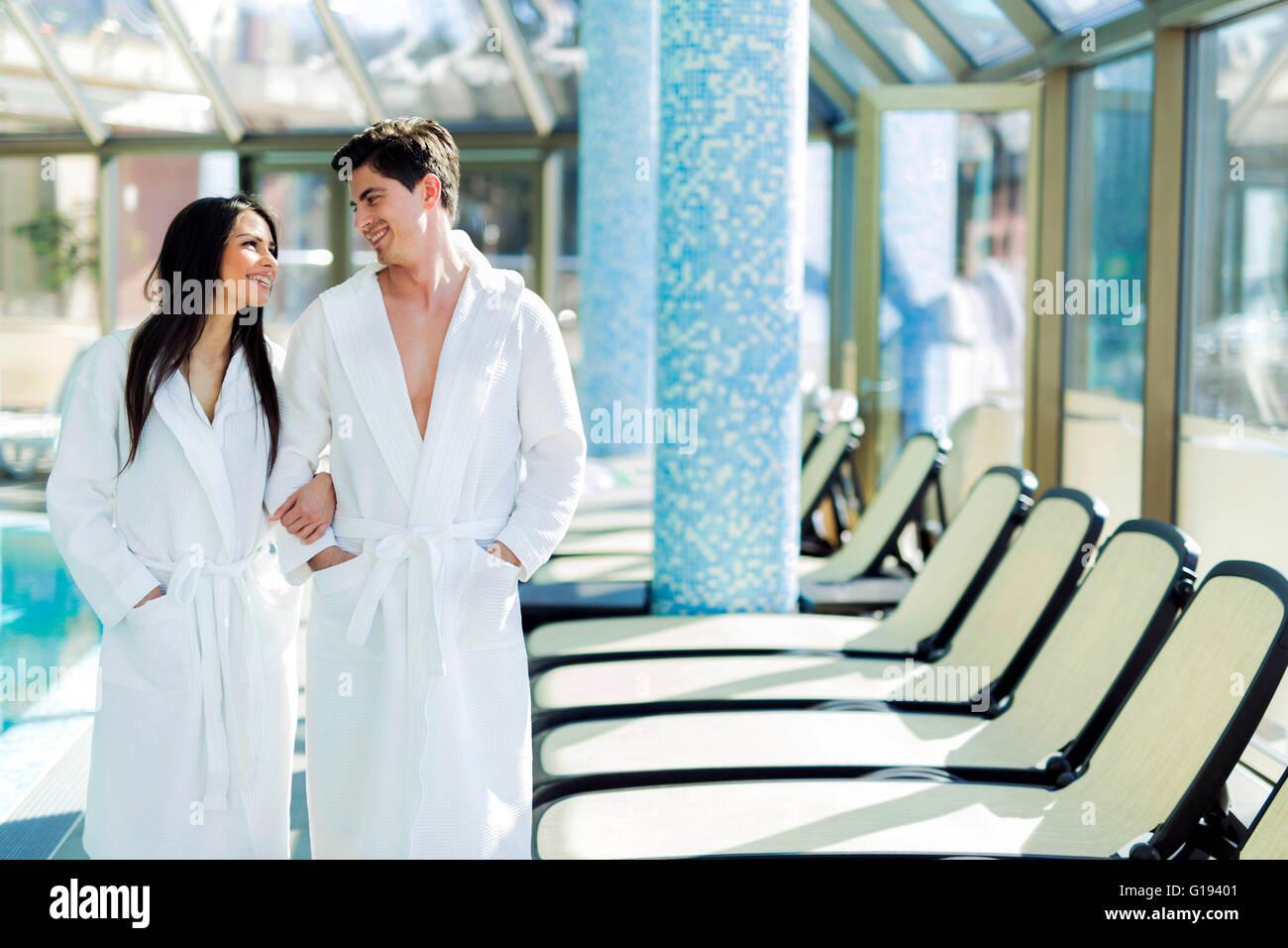 Matura in amore in piedi accanto ad una piscina in un accappatoio e rilassante Immagini Stock
