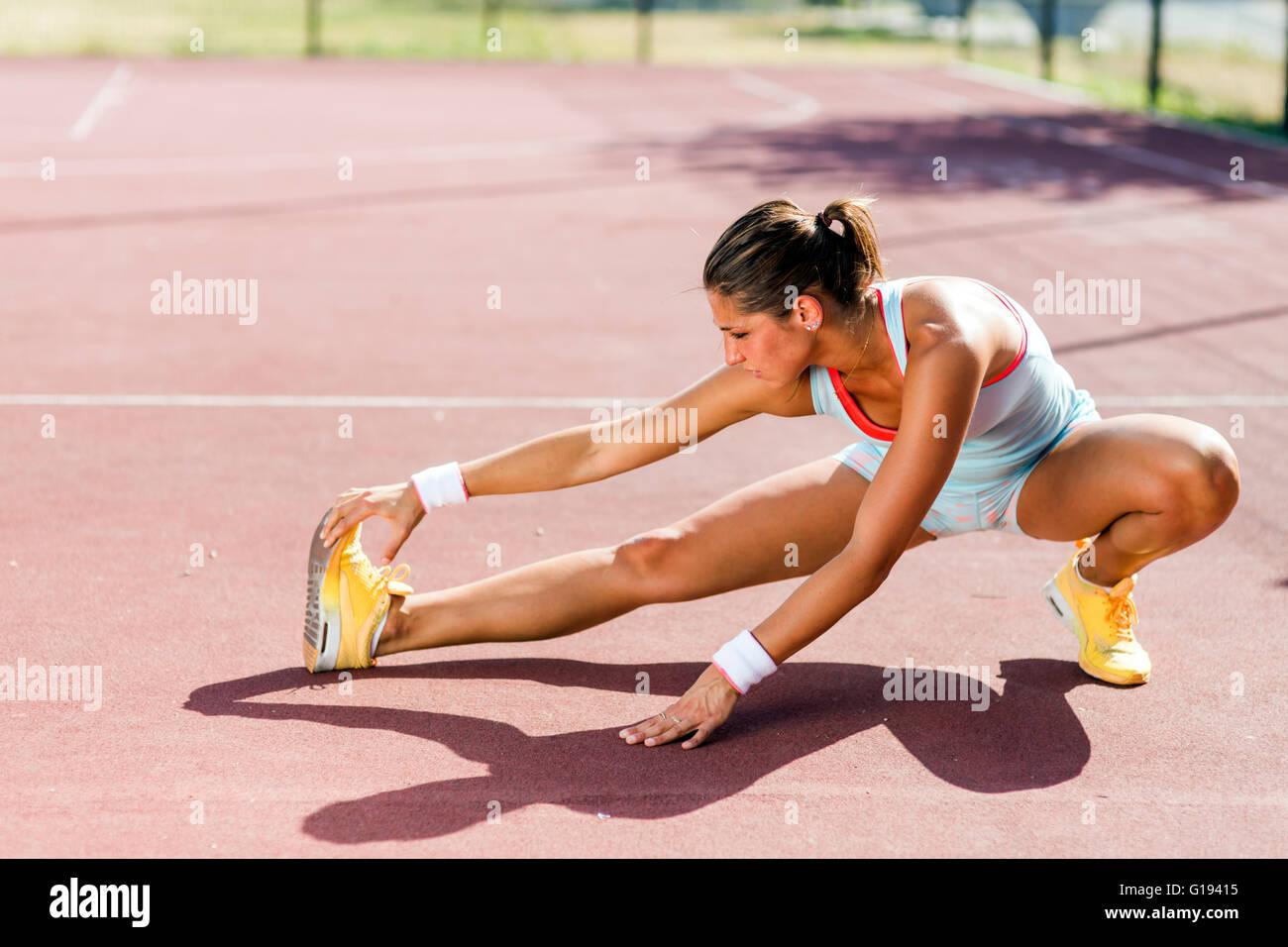 Bellissima giovane donna atletica stretching in estate prima di eseguire Immagini Stock