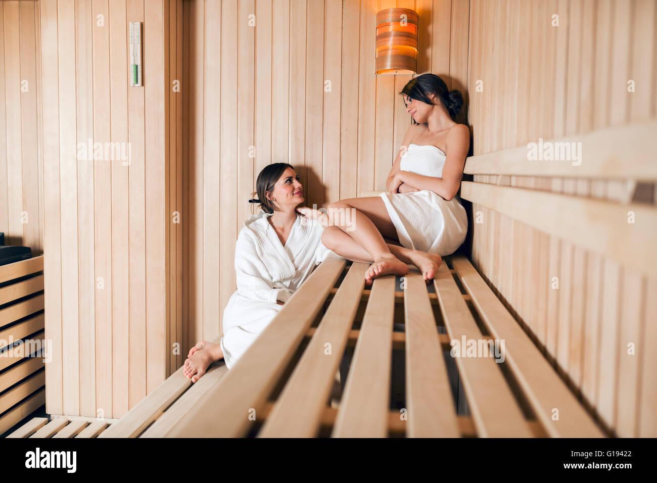 Due montare e belle donne rilassante in una sauna Immagini Stock