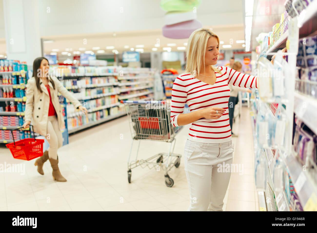 Bella donna di acquisto di prodotti per la cura del corpo nel supermercato Immagini Stock
