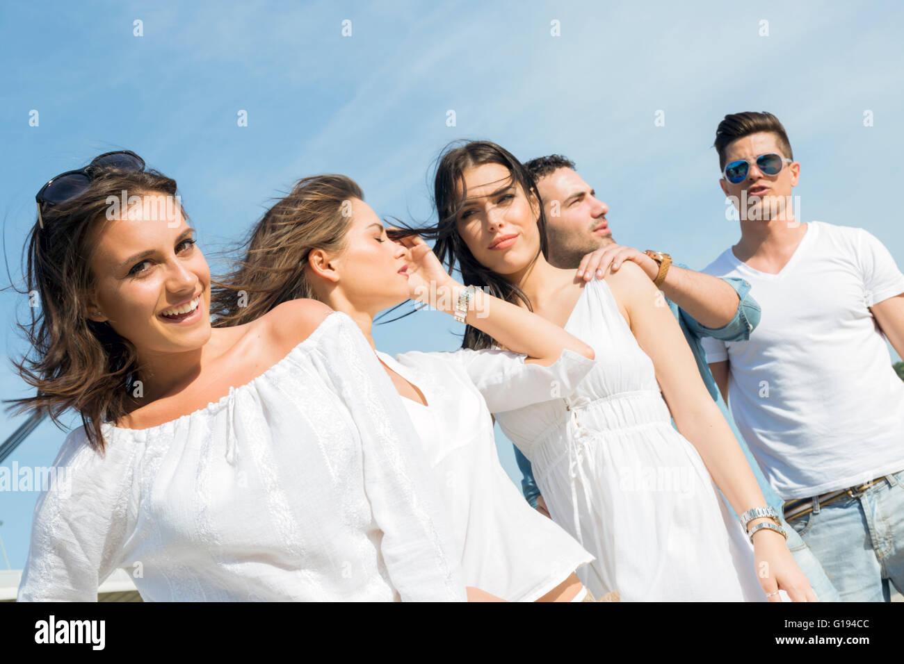 I giovani sulla spiaggia in posa con il vento che soffia i loro capelli Foto Stock