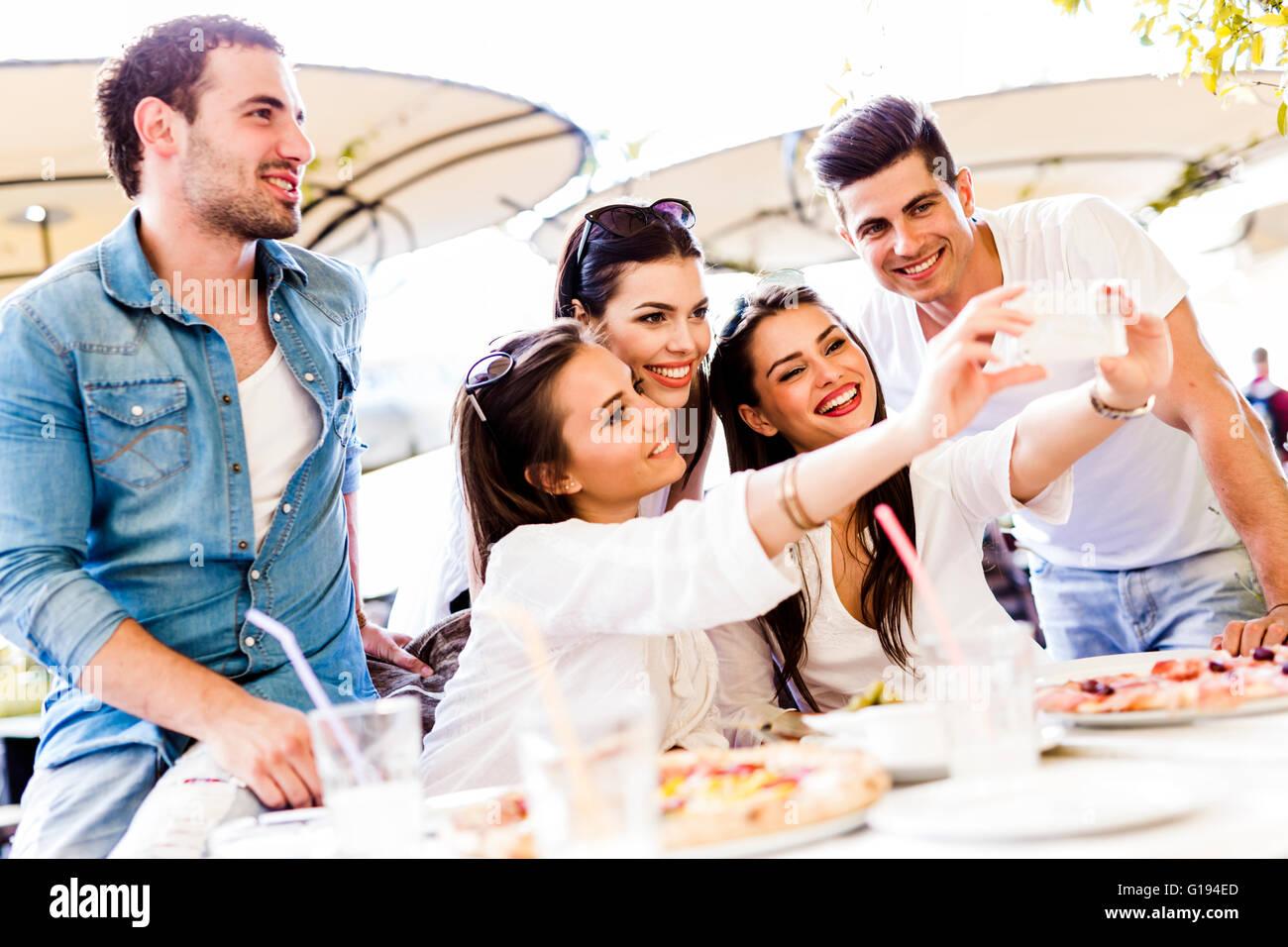 Un gruppo di giovani belle persone sedute in un ristorante e prendendo un selfie mentre sorridente Immagini Stock