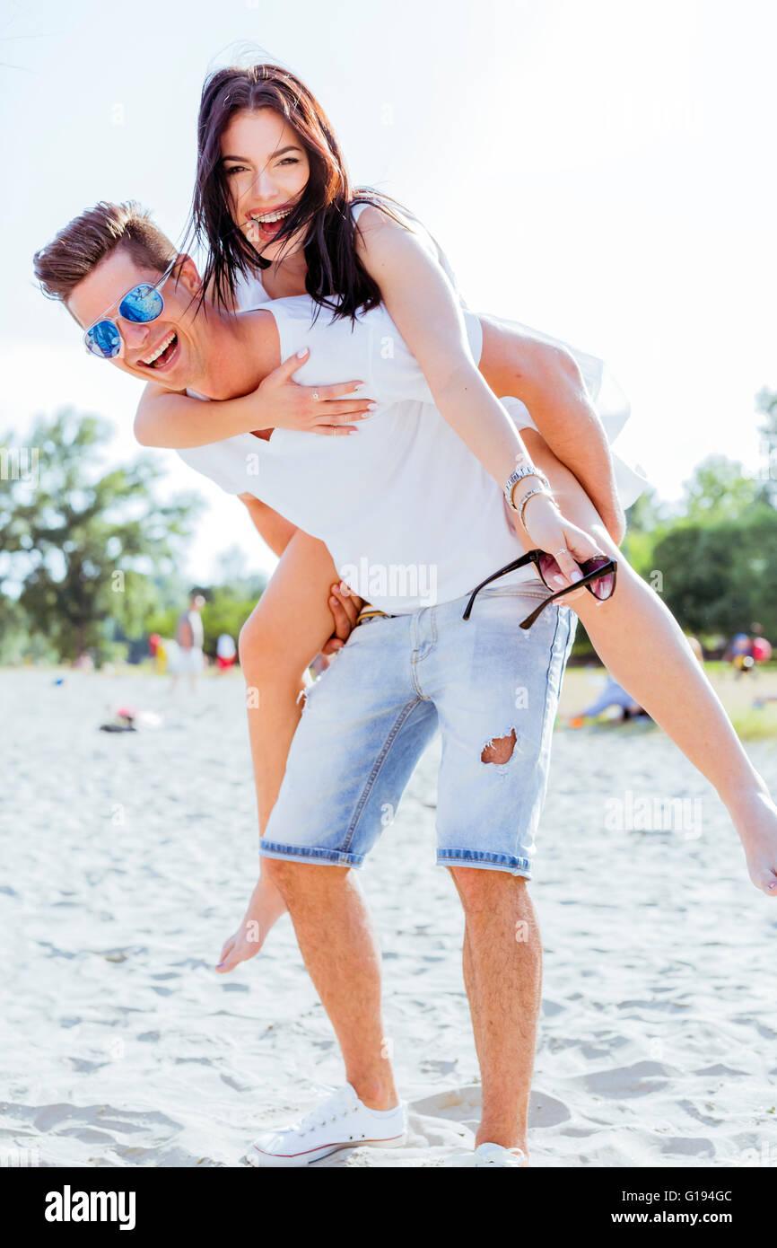 Giocoso giovane godendo le loro vacanze estive come l'uomo porta la donna piggyback Immagini Stock