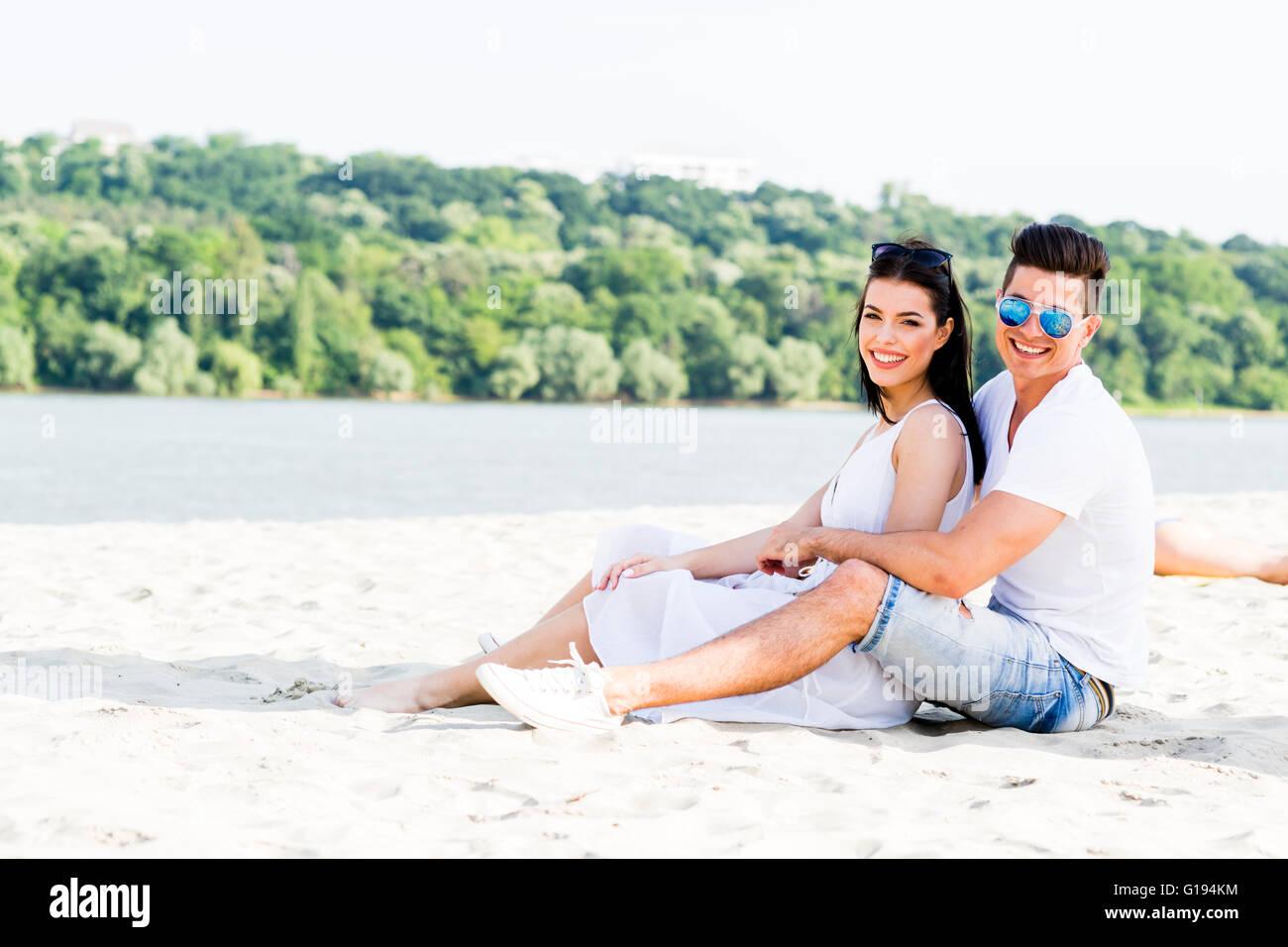 Romantico coppia giovane in amore seduta a una spiaggia sabbiosa e sorridente Immagini Stock