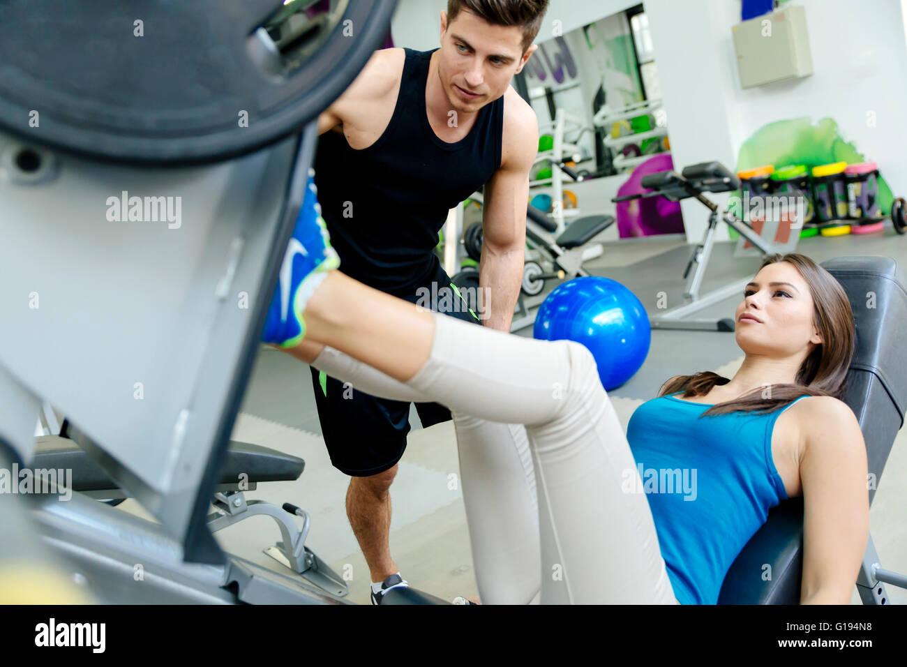 Bella donna gamba facendo esercizi in palestra con l'aiuto di personal trainer Immagini Stock