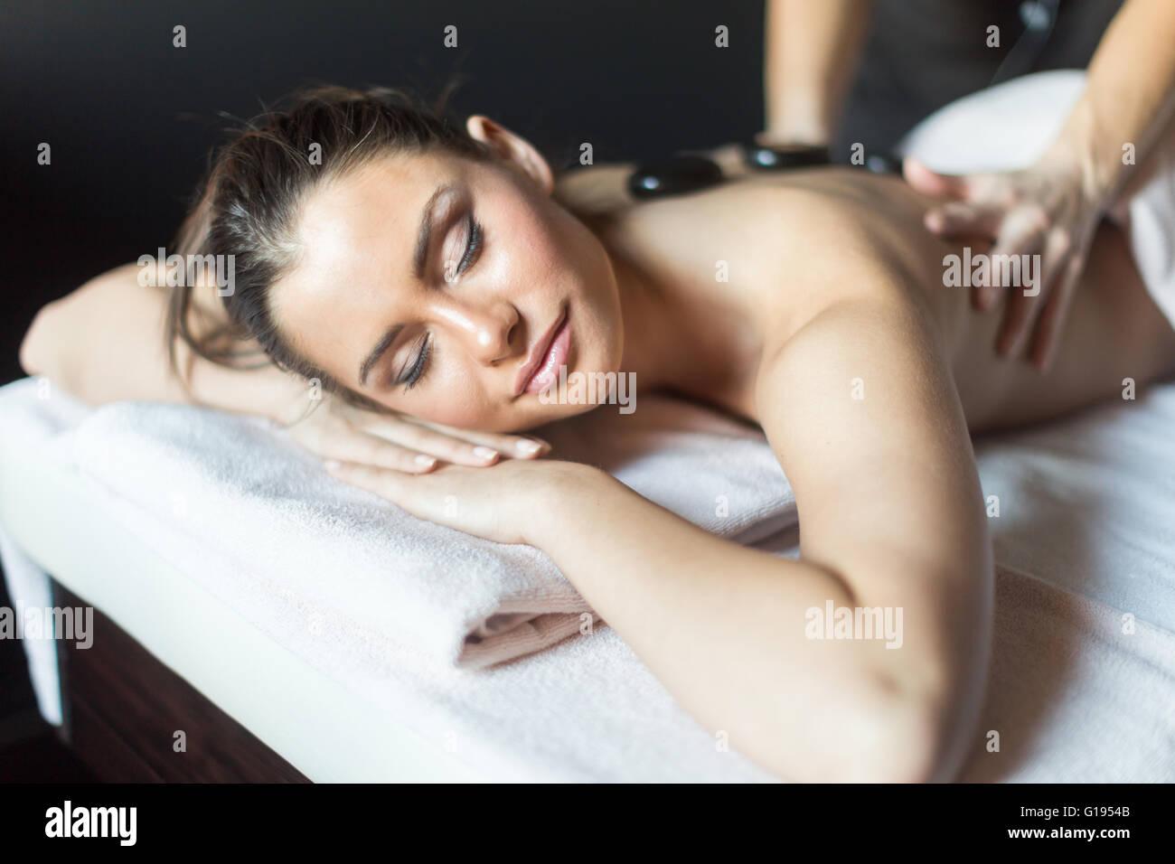 Giovane e bella signora di essere massaggiato con pietre calde sulla schiena Immagini Stock