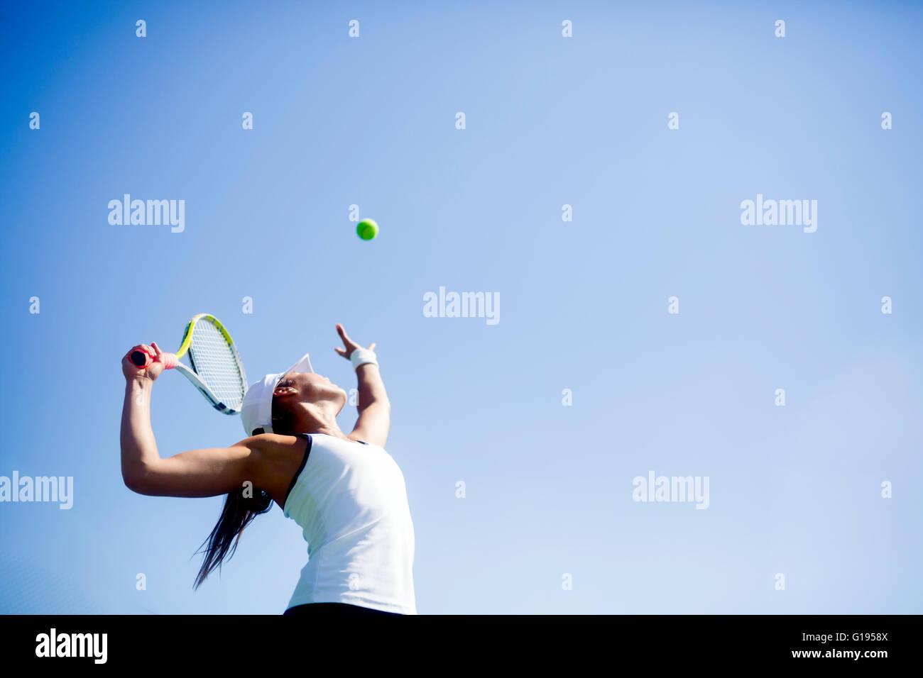 Bellissima femmina giocatore di tennis che serve per esterno Immagini Stock