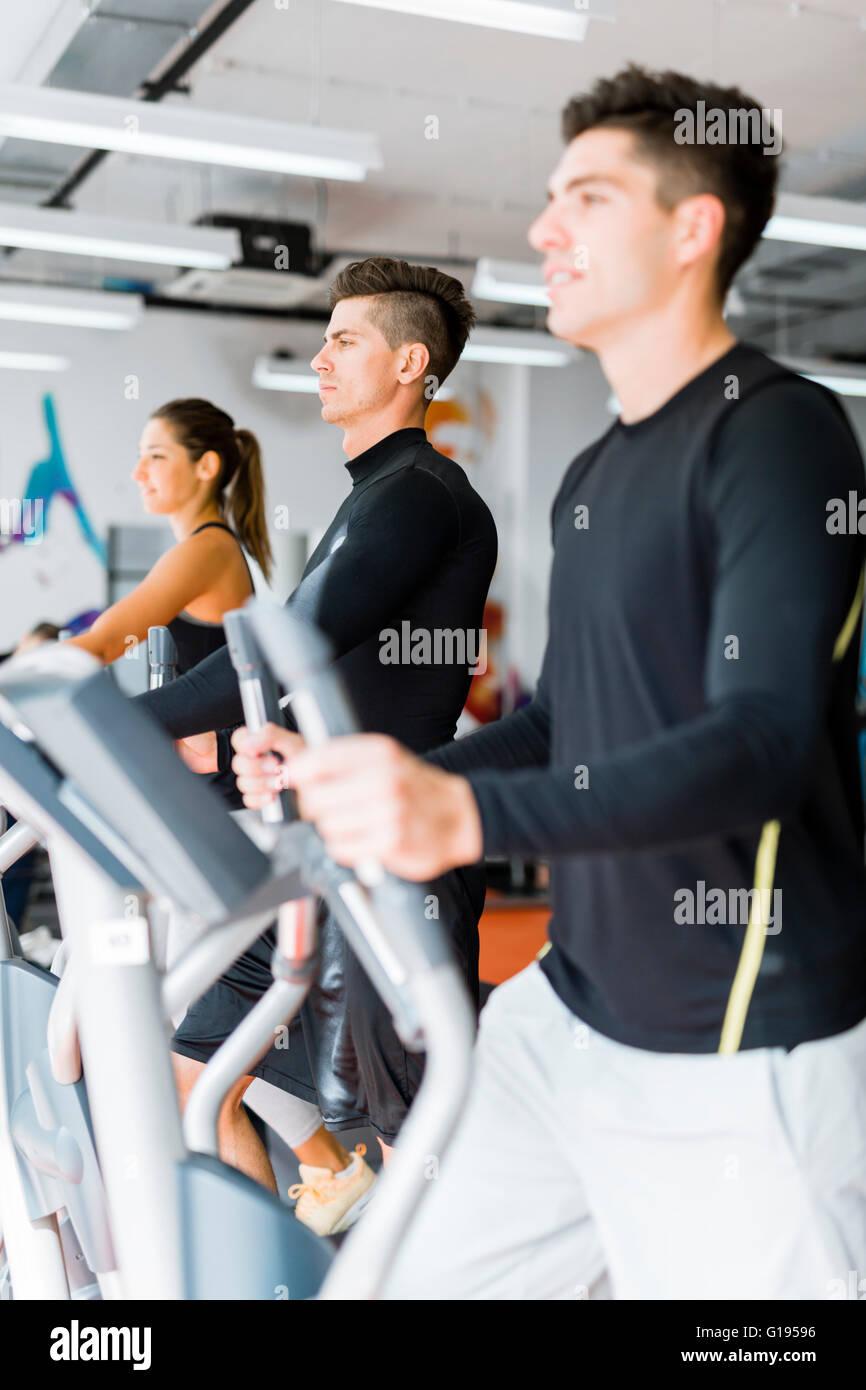 Giovani e sani, un gruppo di persone che lavorano su un trainer ellittico in un centro fitness Immagini Stock