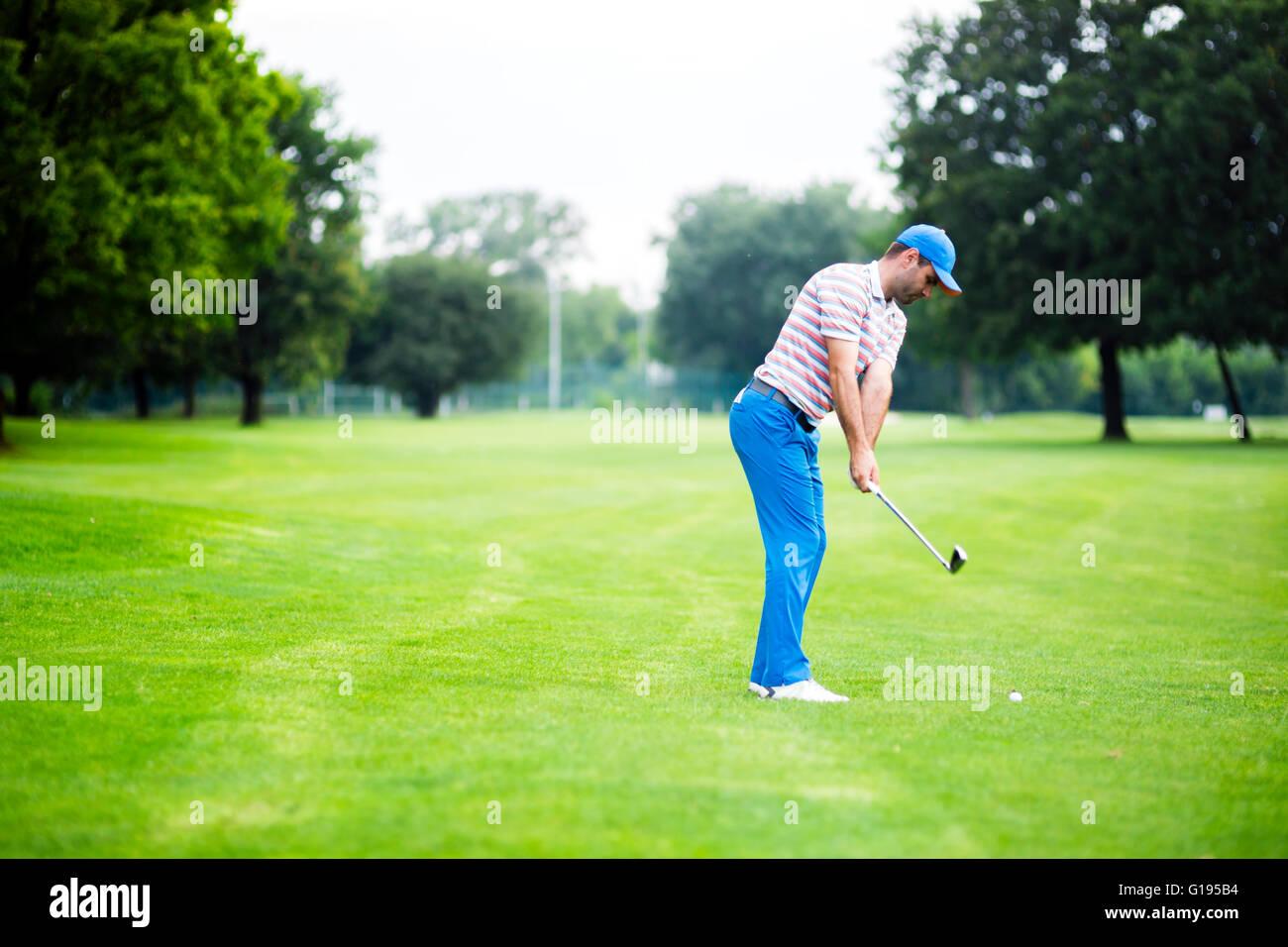 Il Golfer pratica e concentrare prima e dopo aver girato durante una bella giornata di sole Immagini Stock