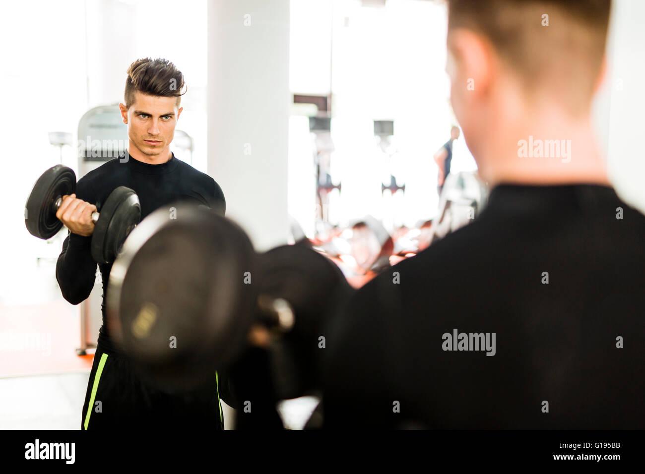 Muscolare giovane uomo che lavora in una palestra e sollevamento pesi con la sua riflessione che mostra in uno specchio Immagini Stock