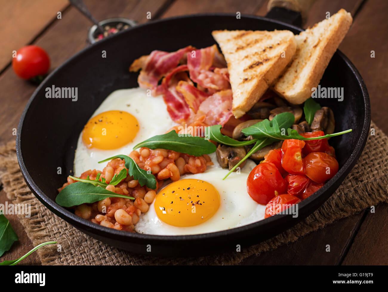 Prima colazione inglese - uovo fritto, fagioli, pomodori, funghi, bacon e toast Immagini Stock