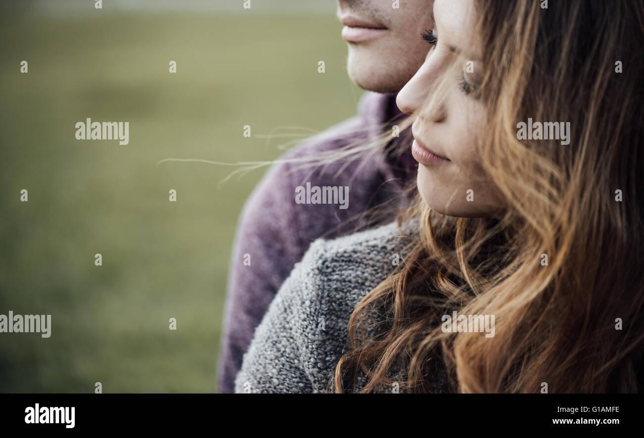 Giovani amare giovane all'esterno seduta su erba, avvolgente e guardando lontano, di futuro e di concetto di Immagini Stock