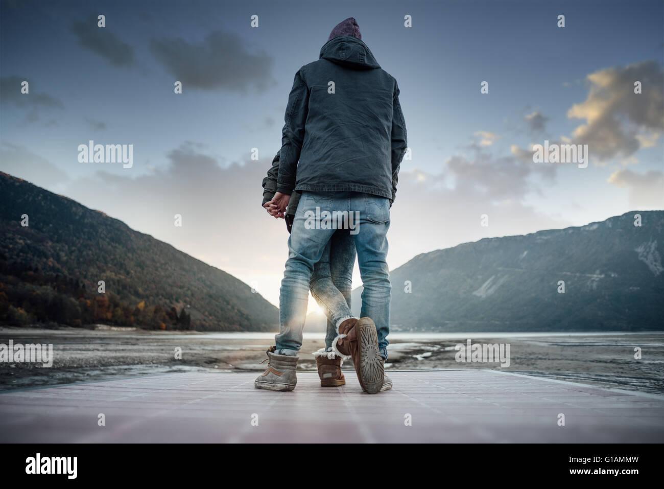 Giovane romantico amare giovane su un molo vista posteriore, paesaggio naturale sullo sfondo Immagini Stock