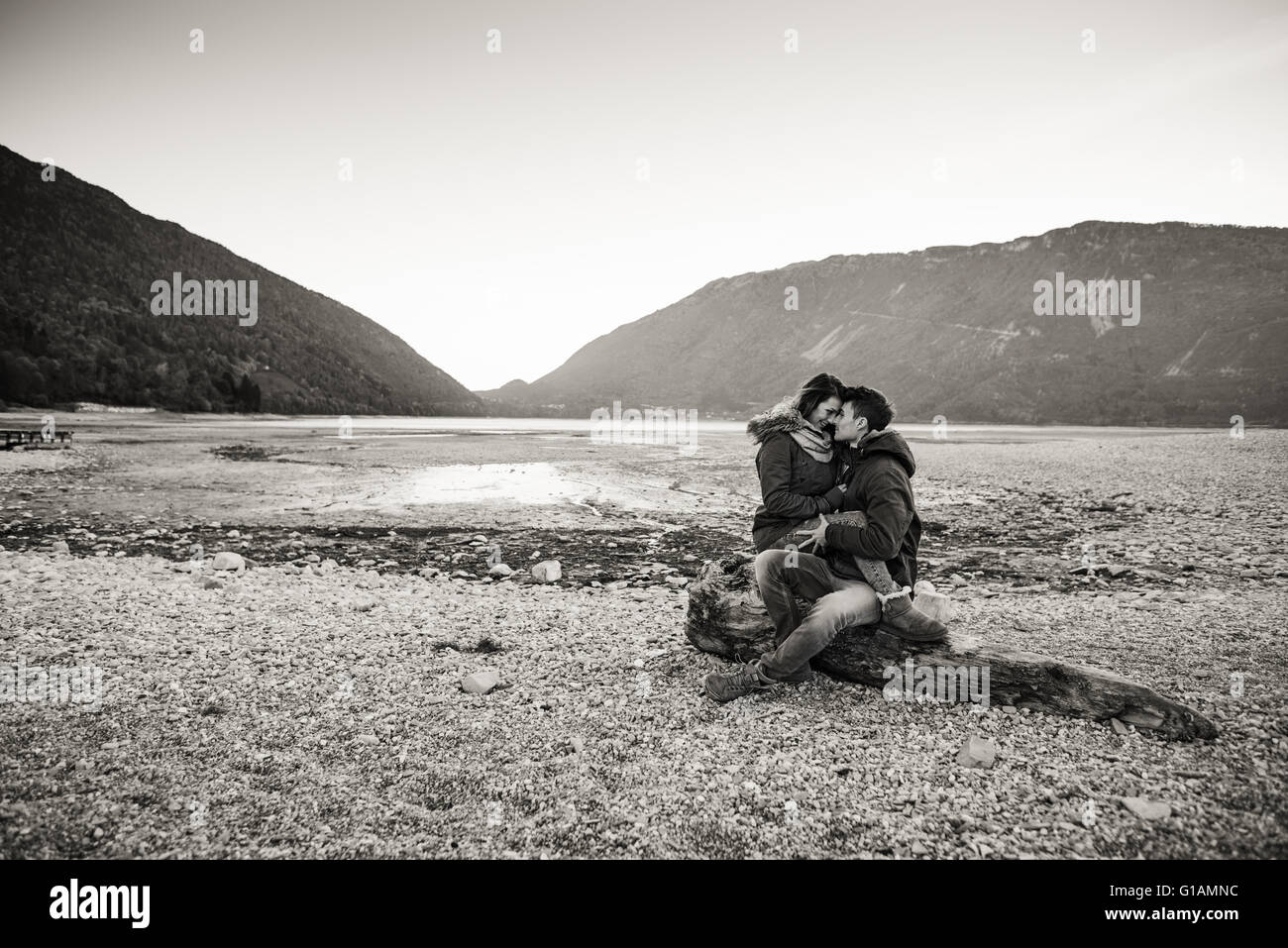 Coppia giovane avente una data romantica al lago, stanno abbracciando e seduta su un tronco sulla spiaggia, di amore Immagini Stock