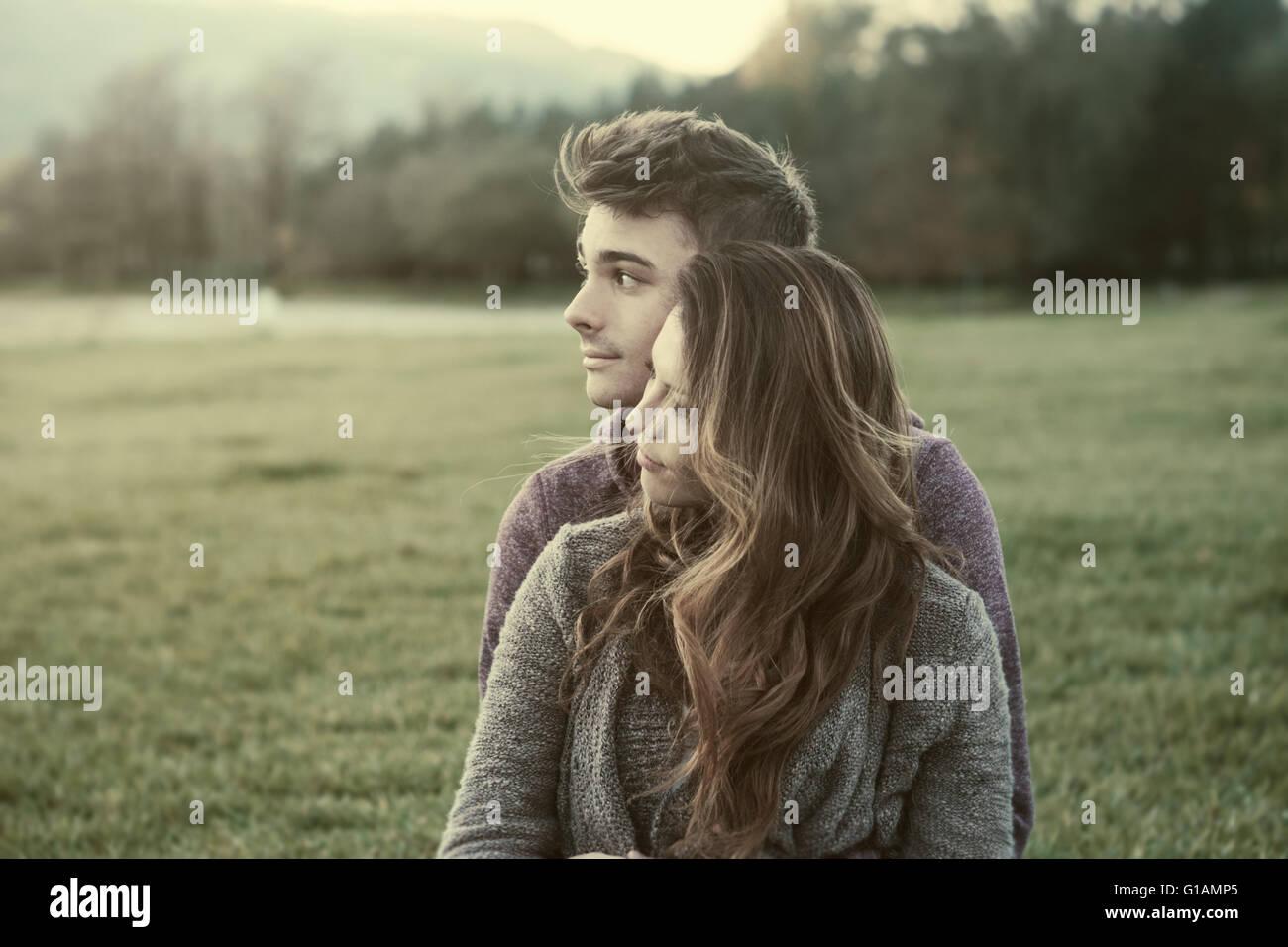 Giovani adolescenti all'aperto, seduti su erba e coccole, egli è abbracciando la sua fidanzata, relazioni Immagini Stock