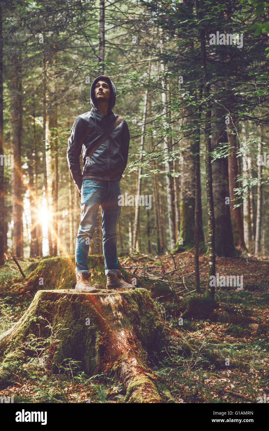 Fiducioso giovane uomo in piedi nella foresta, libertà e individualità concept Immagini Stock