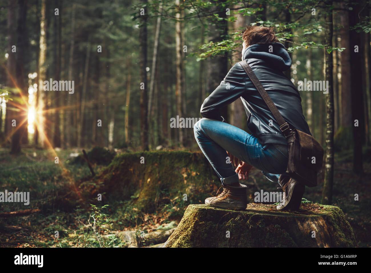 Giovane uomo bello esplorare la foresta e guardandosi attorno, della natura e del concetto di libertà Immagini Stock