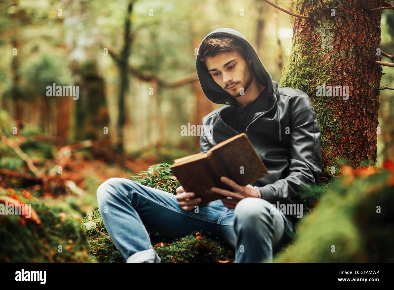 L'uomo della lettura in natura e relax all'aperto, libertà e individualità concept Immagini Stock