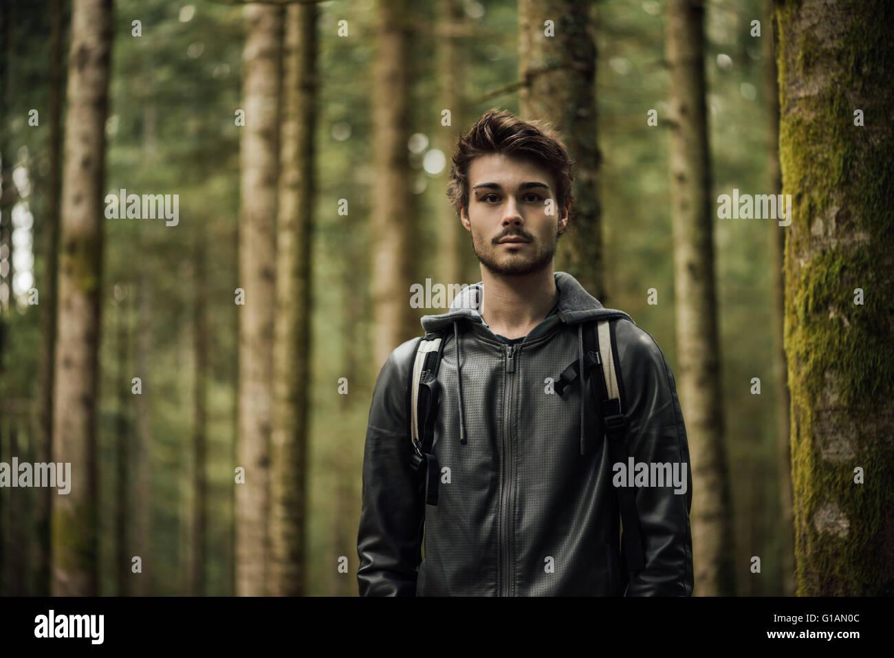 Giovane uomo bello esplorare una foresta, sta guardando la fotocamera Immagini Stock