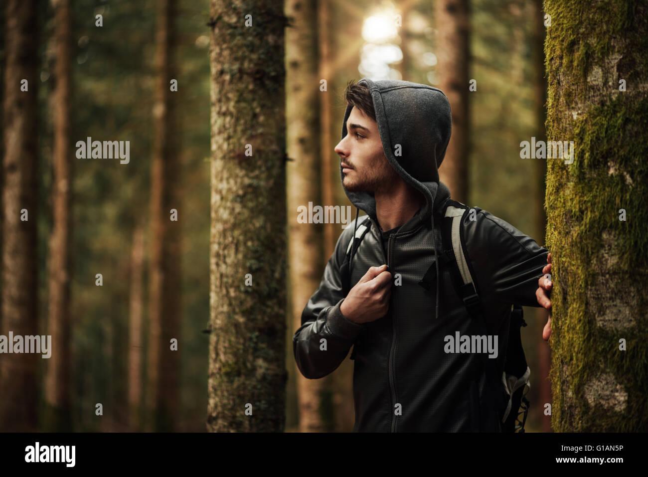 Giovane uomo bello camminare in una foresta e guardandosi attorno, la natura e il concetto di esplorazione Immagini Stock