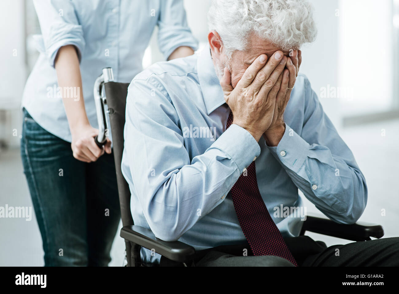 Triste premuto uomo in sedia a rotelle con la testa nelle mani di una donna sta prendendo cura di lui Immagini Stock