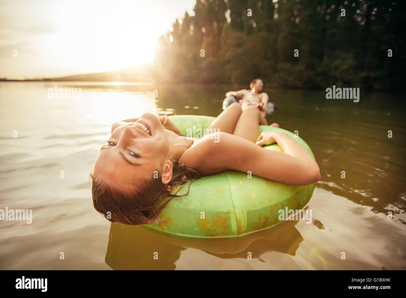 Closeup ritratto di sorridente ragazza giovane galleggianti in un innertube con un uomo a sfondo in un lago. Giovane Foto Stock