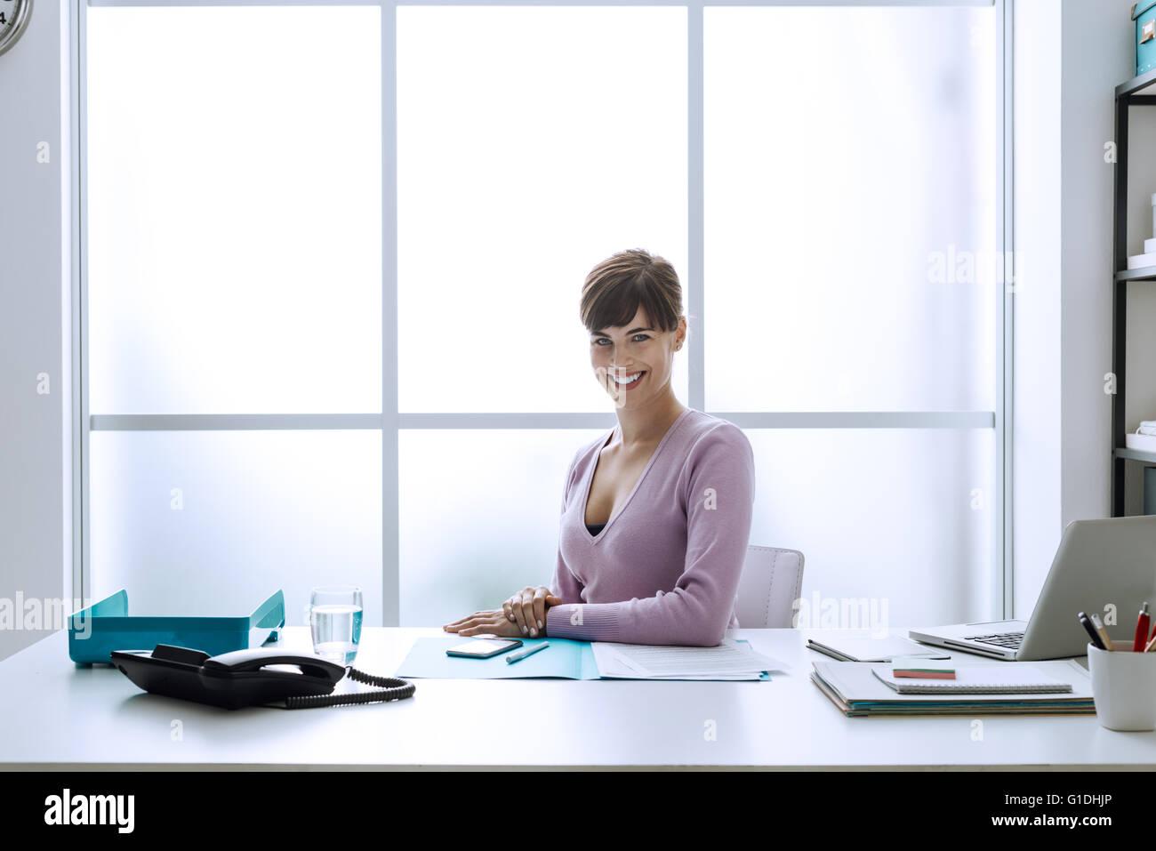 Fiducioso sorridente giovane imprenditrice nel suo ufficio, guarda la fotocamera e seduti alla scrivania Immagini Stock